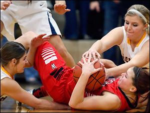 Archbold's Winter Fricke (10), left, and Alexa Coressel (20), right, battle Wauseon's Alyssa Reed (21) for a loose ball during a basketball game.