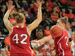 BGSU's Alexis Rogers passing through MU defenders #42, Jessica Rupright, and #22, Kristin Judson, in the first half.  Bowling Green State University's women's basketball team hosts the team from Miami University in Bowling Green.