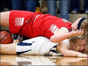 Wauseon's Annette Stidham (43) falls flat on Archbold's Hannah Hesterman (22) while fighting for  rebound during a basketball game.