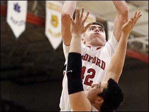 Bedford's Jeremiah Harris (42)  takes a shot against Ann Arbor Pioneer's Ethan Luke Spencer (21).