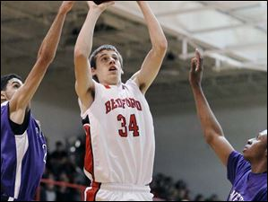 Bedford's Reed Nagley (34) takes a shot against Ann Arbor Pioneer's Jibreel Hussein (23) and Forrest Neal (34).