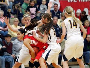 Archbold defenders Alexa Coressel (20), Darian Oberlin (21), and Taylor Coressel (14) surround Wauseon's Sariah Yackee (15)  during a basketball game.