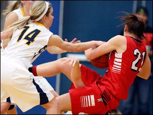 Archbold's Cassidy Williams (3), bottom,  battles Wauseon's Alyssa Reed (21) for the ball during a basketball game.