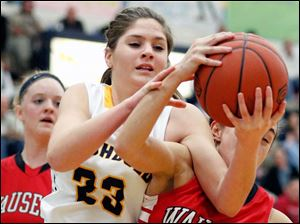Archbold's Jesse Fidler (23) battles  Wauseon's Haley Archibeque (13) for a rebound during a basketball game.