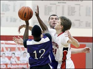 Bedford's Dylan Barr (24) defends against Ann Arbor Pioneer's Kelsey Wallace (12) and Aedan York (4).