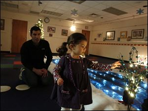 Jamie Karubas, of Perrysburg, left, watches as his daughter Isabel, 1, abandons her paper plate