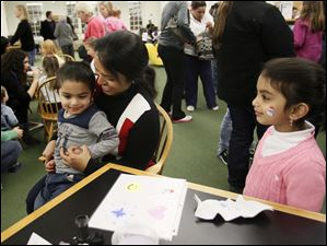 Sanjana Brahme, of Perrysburg, center, holds her son Shubham, 2, for a face painting session.