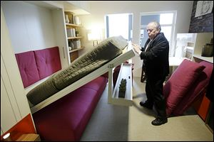 Jack Sproule tries out a fold-down bed in a 325 square foot model apartment at an exhibit called