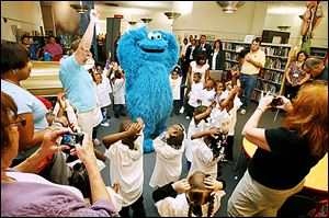 Cookie Monster from 'Sesame Street' leads  Toledo Head Start students in a singalong game as parents and teachers snap photos at Toledo-Lucas County Public Library.