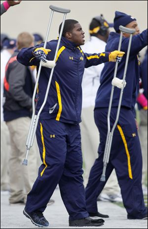 Former University of Toledo football player T.J. Fatinikun supports his teammates from the sideline last season.