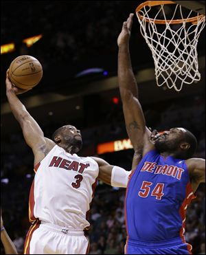 Miami Heat guard Dwyane Wade goes up for a shot against Detroit Pistons forward Jason Maxiell tonight in Miami.