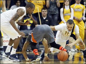 University of Toledo guard Josh Lemons (11) steals the ball from Bowling Green State University guard Jordon Crawford.
