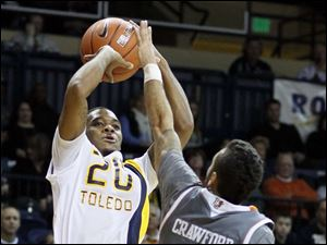University of Toledo guard Julius Brown takes a shot over Bowling Green State University guard Jordon Crawford.
