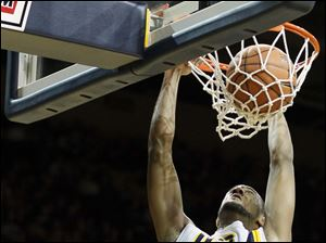 University of Toledo forward Matt Smith dunks the ball over Bowling Green State University forward James Erger.