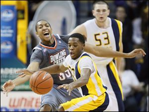 University of Toledo guard Julius Brown (20) steals the ball from  Bowling Green State University  forward Cameron Black.
