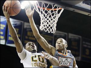 University of Toledo guard Julius Brown (20) takes a shot against Bowling Green State University forward Richaun Holmes (22).