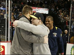 University of Michigan football player Elliot Mealer, left, hugs teammate Jordan Kovacs, as Kevin Koger has a laugh after Kovacs dropped the ceremonial puck before the game  Mealer is from Wauseon, Kovacs from Oregon Clay and Koger from Toledo Whitmer High School.