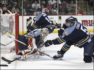 Toledo Walleye goalie Kent Simpson, 35, gets help as teammate Wes O'Neill, 5, sweeps the puck away from the net.