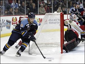 Toledo Walleye player Nino Musitelli, 7, skates the puck behind Bakersfield Condors goalie Brian Stewart, 41.