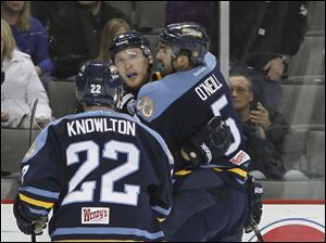 Toledo Walleye players Patrick Knowlton, 22, Doug Clarkson, 9, and Wes O'Neil, 5, celebrate Clarkson's goal.