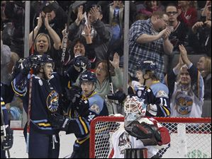 Toledo Walleye players Trevor Parkes, 8, Joey Martin, 14, and Andrej Nestrasil, 11, celebrate Parkes' goal.
