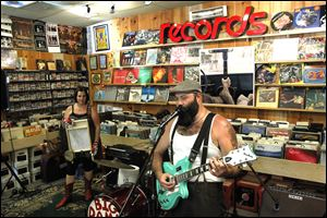 Reverend Peyton's Big Damn Band plays an in-store concert. Breezy Peyton, left, plays with Rev. Peyton, right.