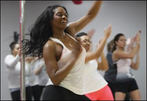Reflected through a mirror, exercise trainer Shanika Kynard works out at Exquisite Physiques.