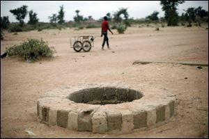 A man pulls a cart past a well where several bodies were dumped in Sevare, north of Mali's capital, Bamako. A witness told The Associated Press that he saw soldiers fatally shoot at least three people at a nearby bus stop and dump their bodies in the well.