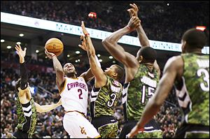 The Cavaliers' Kyrie Irving (2) shoots against the Raptors' Landry Fields, left, Kyle Lowry (3), and Amir Johnson (15) during the first half.