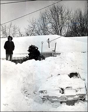 Dave Rickenberg of Liberty Center, Ohio, stands atop a seemingly mountainous snowdrift at his home, where he spent four hours digging out the car in his driveway.
