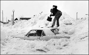 Toledoan Jerry Ludwig attempts to dig his car out of a snow pile at the Glenbyrne Shopping Center parking lot.
