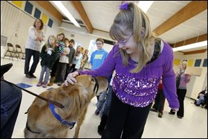 Quincy, a 4-year-old golden retriever service dog owned by Benny Wilkerson, shares affection with third grader Emily Wells at Whiteford Elementary School in Ottawa Lake.