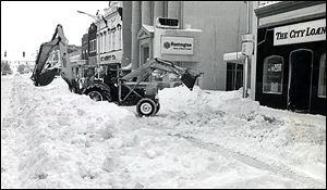 A backhoe operator works at clearing snow on South Main Street in downtown Bowling Green after the blizzard of 1978. Crews stopped only long enough to refuel.