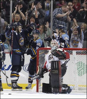Toledo Walleye players Trevor Parkes, 8, Joey Martin, 14, and Andrej Nestrasil, 11, celebrate Parkes' goal against Bakersfield Condors goalie Brian Stewart.