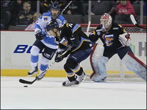 The Walleye's Joey Ryan clears the puck in the first period in front of goalie Jordan Pearce.