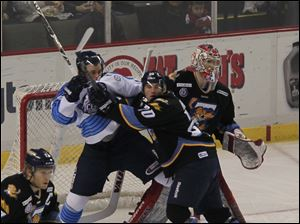 Walleye defenseman Phil Rauch keeps the Icemen's Mark Cody out of the line of sight of Walleye goalie Jordan Pearce in the third period.