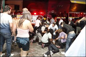 People help an injured man, victim of a fire in a club in Santa Maria city, Rio Grande do Sul state, Brazil, today.