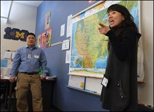 Pen Tsou, an eighth-grade teacher at Old Orchard Elementary School in Toledo, left, and Xing Xu Wang, a teacher from the Fushun Experimental Middle School in China, talk about geography in Mr. Tsou's class.  A group of Chinese students and educators are visiting Old Orchard.