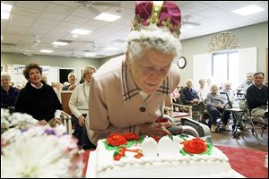 On the occasion of her 100th birthday observance Wednesday, Emma Bonawitt blows out the candles on her centennial celebration cake with friends and family at Senior Star at West Park Place in Toledo. She credits her longevity partially to not smoking