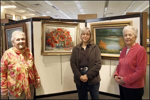 Gloria Sandusky-Mossburg, left, Evelyn Deselms, the Bedford Artists' Club publicity chairman, and Donna Whittaker  stand before some of the works on display at the Bedford Branch Library. Mrs. Sandusky-Mossburg and Mrs. Whittaker are friends as well as club members, and they paint together in Mrs. Mossburg's studio in her Lambertville home. Both say they've been painting since the late 1950s.