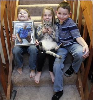 Colin and Kate Brewer, both 6, and brother Toby, 10, with their cat Leroy, deal with the sudden death of their father, Gary Brewer, in December.