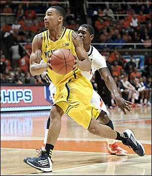 Michigan's Trey Burke, who had 19 points, drives past Illinois' Brandon Paul.