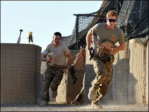 Britain's Prince Harry, right, or just plain Captain Wales as he is known in the British Army, races out from the VHR (very high readiness) tent to scramble his Apache with fellow pilots, during his 12-hour shift at the British-controlled flight-line in Camp Bastion southern Afghanistan in November, 2012.