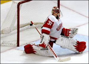 Detroit Red Wings goalie Jimmy Howard watches as a goal by Chicago Blackhawk Nick Leddy trickles into the net during overtime game Sunday in Chicago. The Red Wings lost 2-1.
