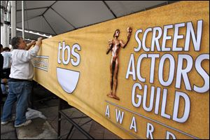 Workers set up signage on the red carpet, Saturday, before the 19th annual SAG Awards Sunday night.