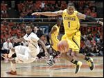 Illinois' D.J. Richardson (1) and Michigan's Glenn Robinson III (1) watch a loose ball during the second half of their NCAA college basketball game, Sunday, Jan. 27, 2013, in Champaign, Ill. Michigan won 74-60. (AP Photo/John Dixon)
