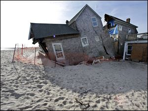 A beach front home that was severely damaged by Superstorm Sandy rests in the sand in Bay Head, N.J.