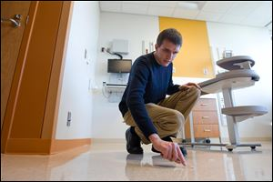 Biologist Daniel Smith swabs the floor in a new hospital room to collect microbial samples at the new University of Chicago Hospital in Chicago. The hospital is not open to the public yet.