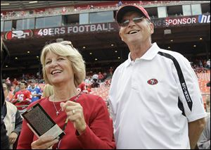 Jackie and Jack Harbaugh, parents of San Francisco 49ers coach Jim Harbaugh and Baltimore Ravens coach John Harbaugh, stand before an NFL football in 2011