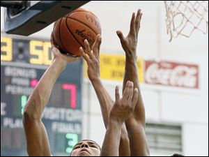 St. John's Jesuit's Marc Loving goes to the net against Rogers' Fadil Robinson.
